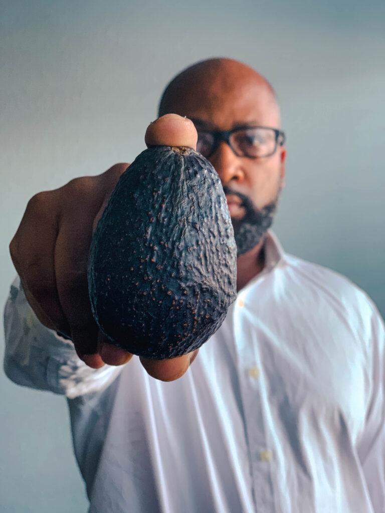 man holding avocado